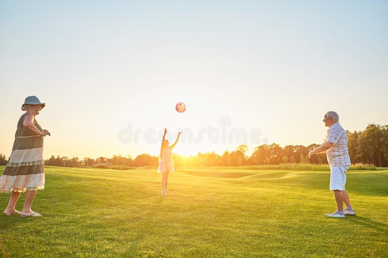 Girl with grandparents playing ball. stock image