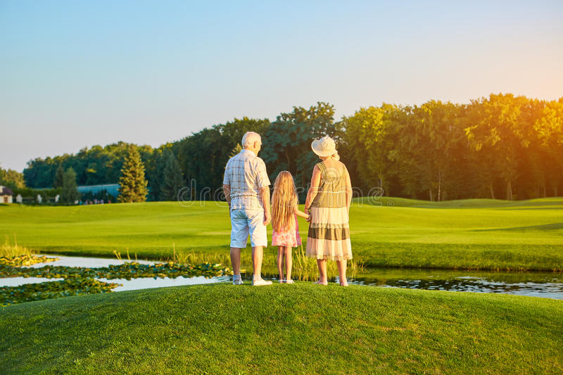 Girl with grandparents, summer. stock photo