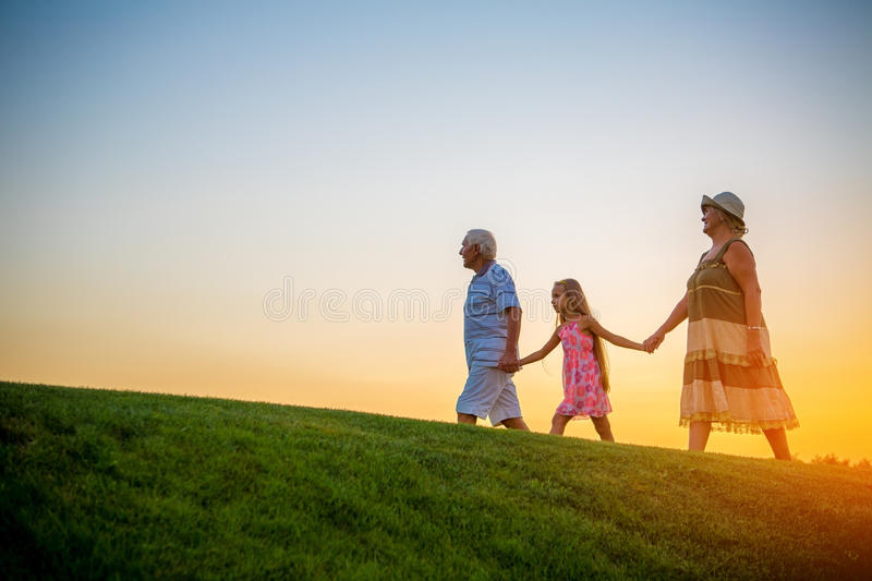 Girl with grandparents at sunset. stock image
