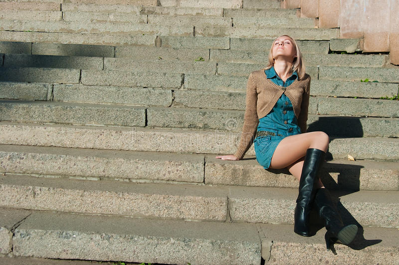 Girl of a granite ladder sitting. The image of the girl of a granite ladder sitting on steps royalty free stock images