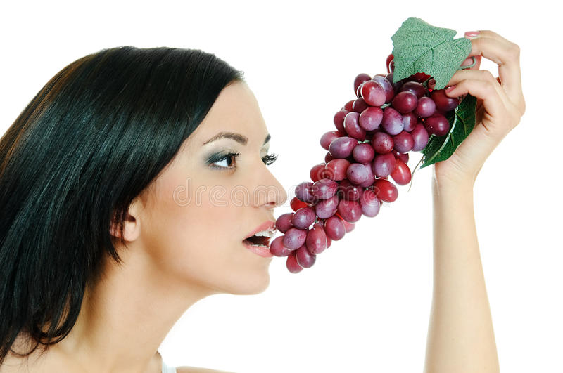 Girl with grapes. Beauty brunette with grapes on white background royalty free stock photo