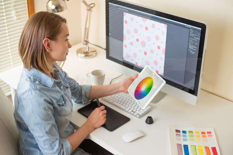 Girl graphic web designer. working on a project. work with color. freelance designer. Graphic designer sitting at work. Illustrator. web designer. freelancer royalty free stock images