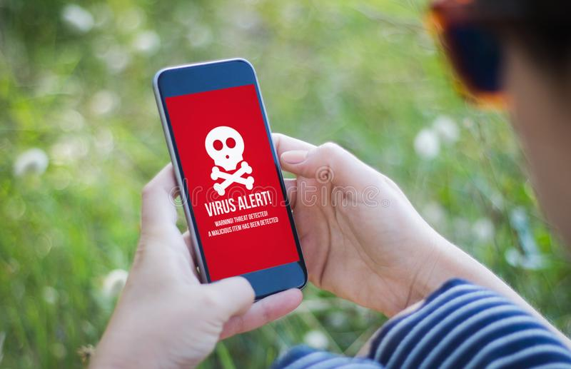 girl in grass holding her smartphone with virus alert royalty free stock photo