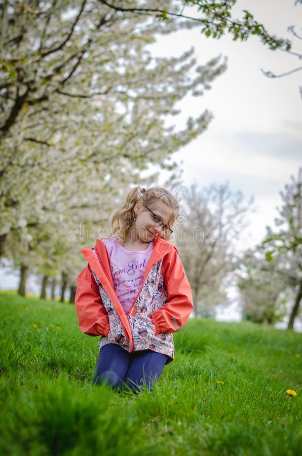 Girl in grass in springtime sitting in the grass stock image