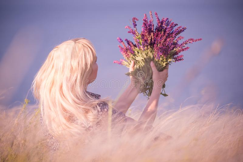 The girl among the grass steppe feather grass with a bouquet of flowers of sage. The atmosphere of outdoor recreation among flower stock photos