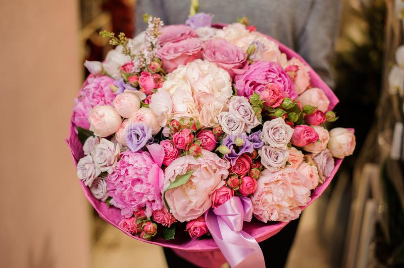 Girl holds a huge bouquet of different pink and purple flowers. Girl in a gray sweater holds a huge bouquet of different pink and purple flowers, decorated with royalty free stock photo