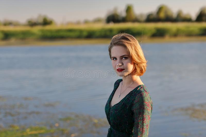 The girl in a green authentic dress walks at sunset on the coast of a reservoir royalty free stock photos