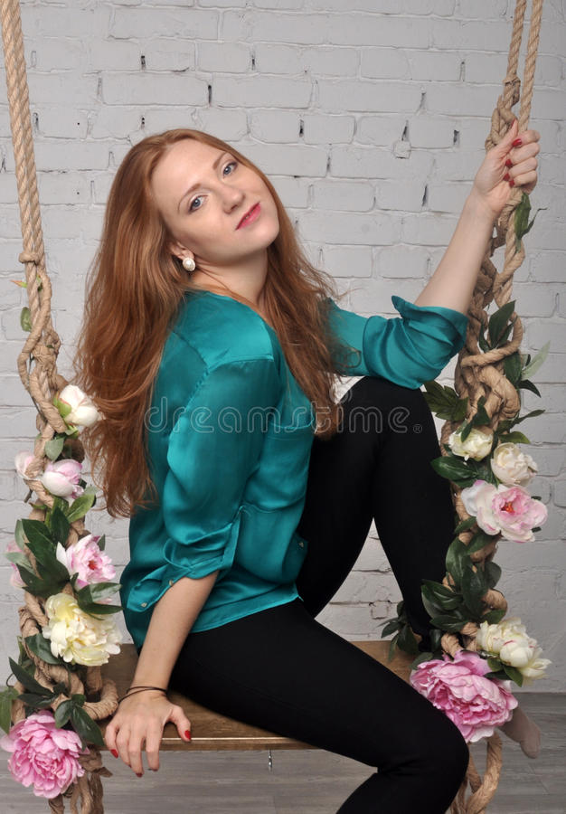 Girl in green blouse on flower swing resting smiling royalty free stock photography