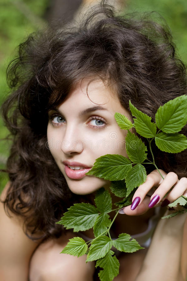 Girl with a green branch. Image of a beautiful girl with a green branch in his hands royalty free stock images