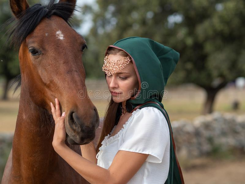Girl with green cape caresses the head of a brown horse. Blonde blue-eyed girl with green cape caresses the head of a brown horse in the field stock images