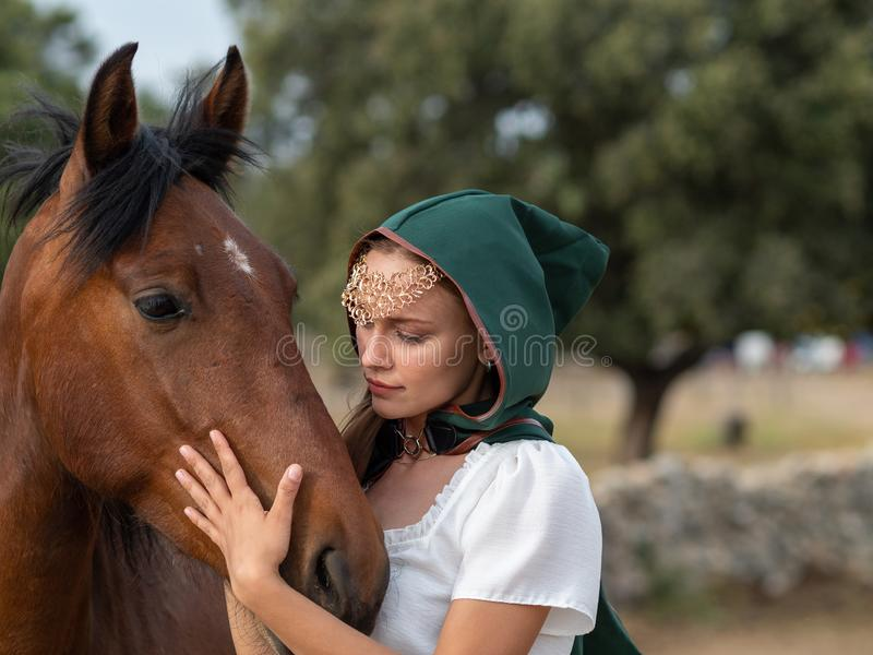 Girl with green cape caresses the head of a brown horse. Blonde blue-eyed girl with green cape caresses the head of a brown horse in the field stock photos