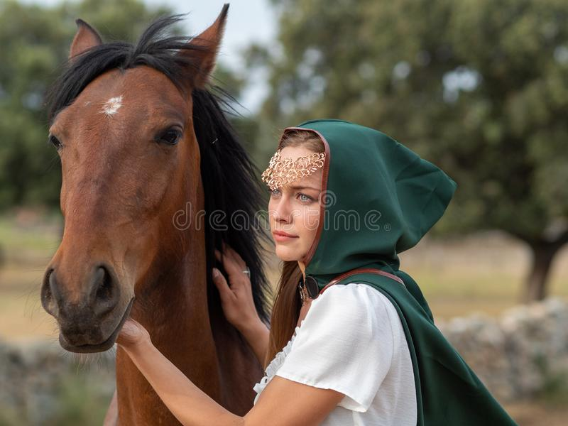 Girl with green cape caresses the head of a brown horse. Blonde blue-eyed girl with green cape caresses the head of a brown horse in the field royalty free stock images