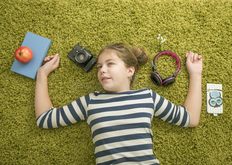 Girl on the green carpert. Girl with the book ,aple , camera end headset on the green carpert royalty free stock image
