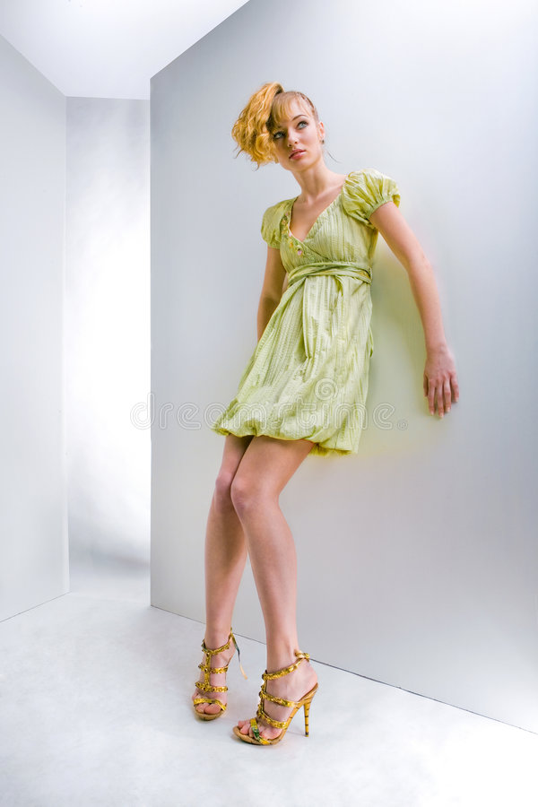 Girl in a green dress. In all growth. Studio stock photo