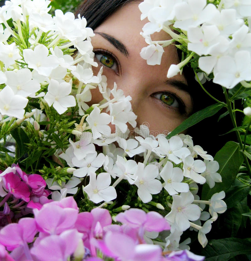 Girl with green eyes in flowers. Portrait of beautiful young woman with green eyes in purple and white flowers. Sparkling look. Bright colors of spring and royalty free stock photos