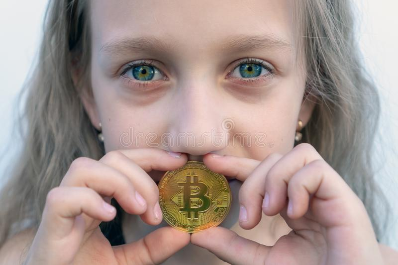 A girl with green eyes holds a bitcoin coin in her mouth. Concept of easy bitcoin investing and trading.  royalty free stock photos