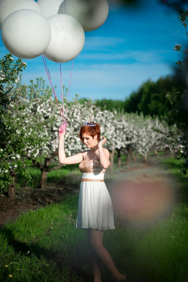 Girl in the green garden with balloons stock photo
