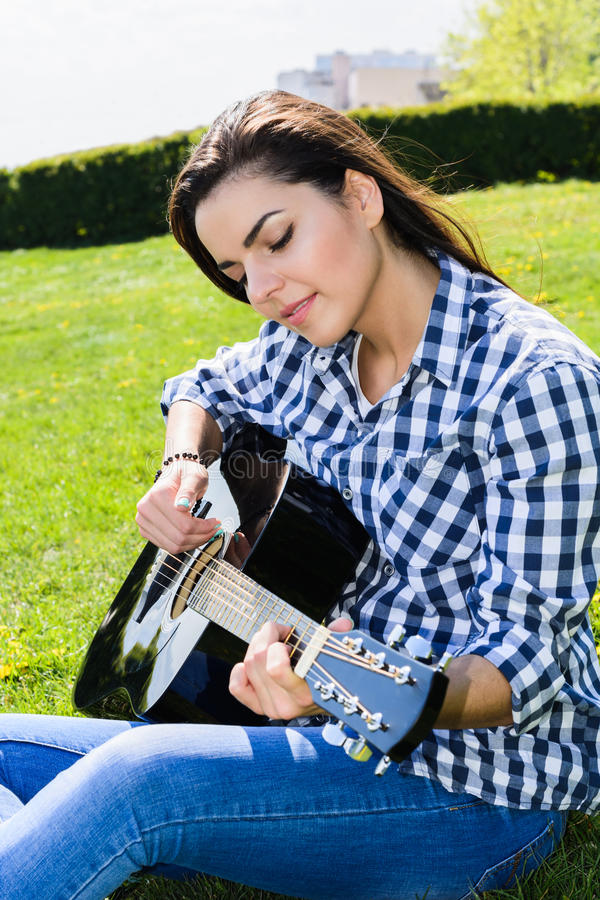 Girl on a green meadow playing guitar royalty free stock photos