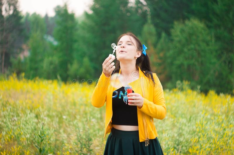 A girl in a green skirt on a flower meadow blowing bubbles royalty free stock images