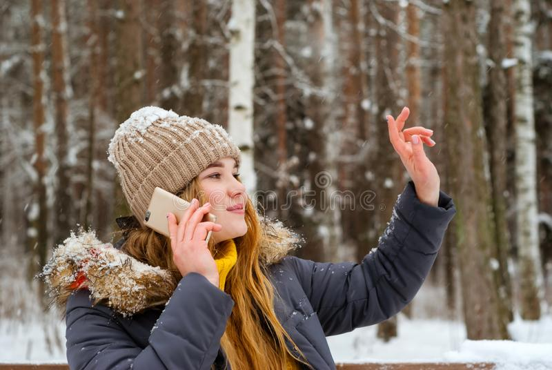 Girl greets someone by hand, talking on the phone in the winter in the open air royalty free stock image