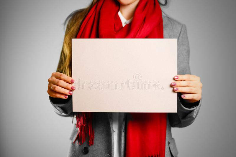 A girl in grey coat and red scarf keeps a beige clean blank sheet of A4. Isolated on grey background.  royalty free stock images