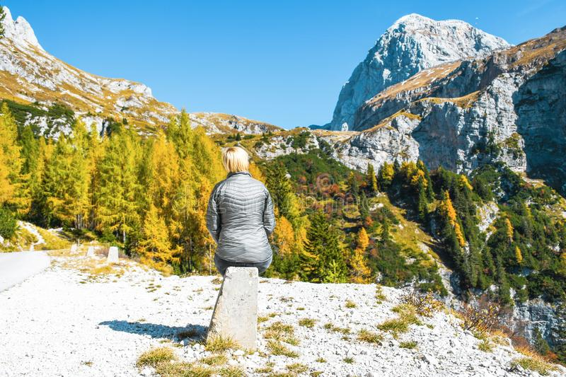 Girl with grey jacket sitting and resting on concrete road pillar on a nice sunny autumn day trip in Julian alps royalty free stock images