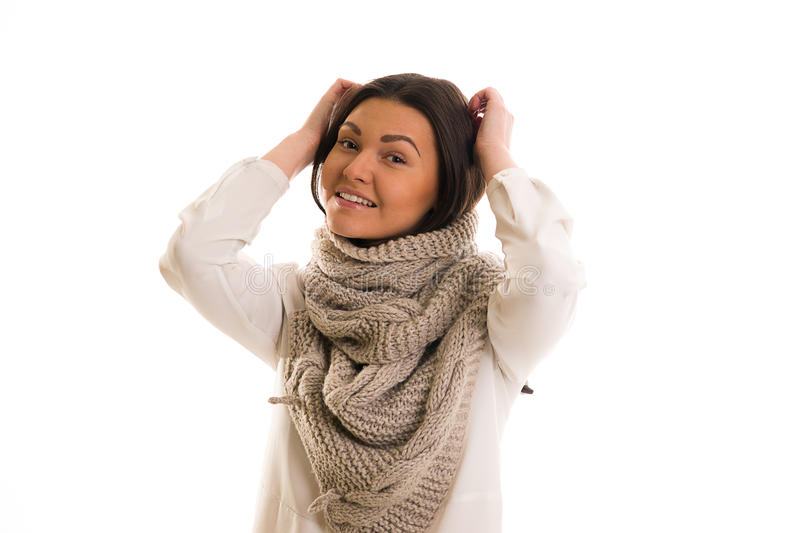 A girl in a grey knitted scarf smiling. A young woman in a grey knitted scarf smiling stock photography