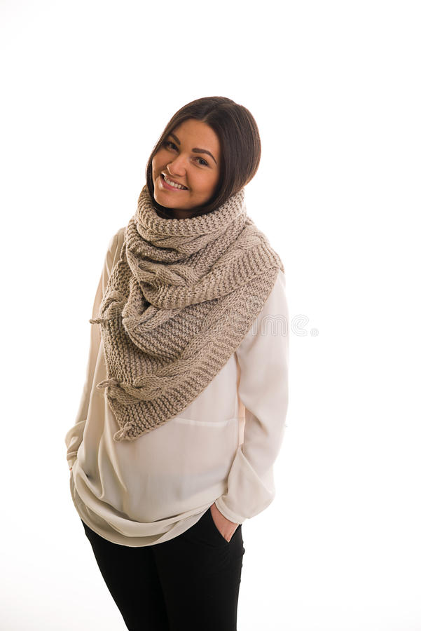 A girl in a grey knitted scarf smiling. A young woman in a grey knitted scarf smiling royalty free stock photography