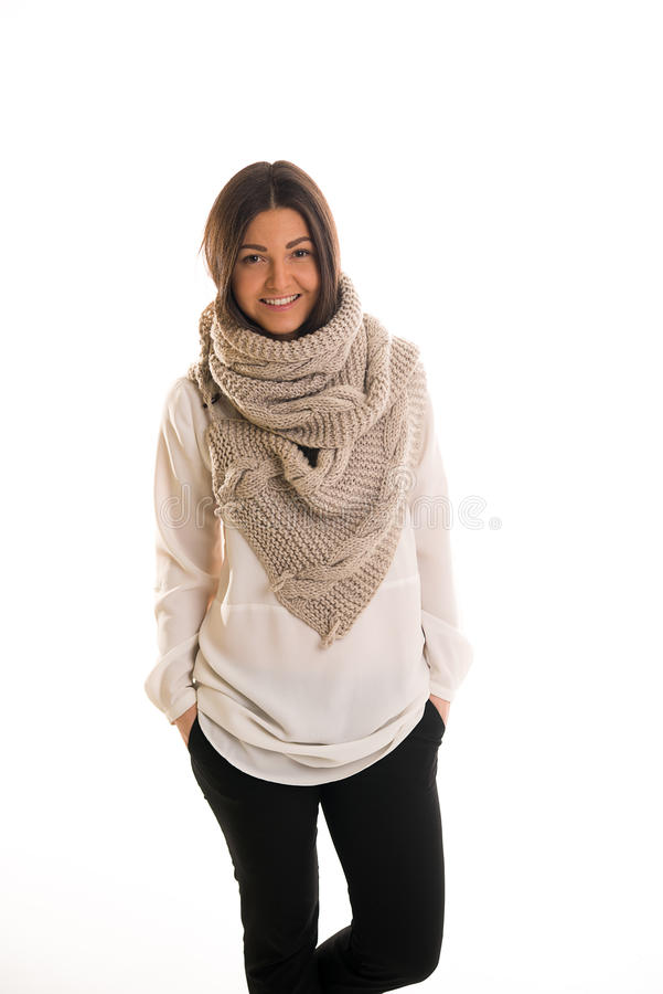 A girl in a grey knitted scarf smiling. A young woman in a grey knitted scarf smiling stock photos