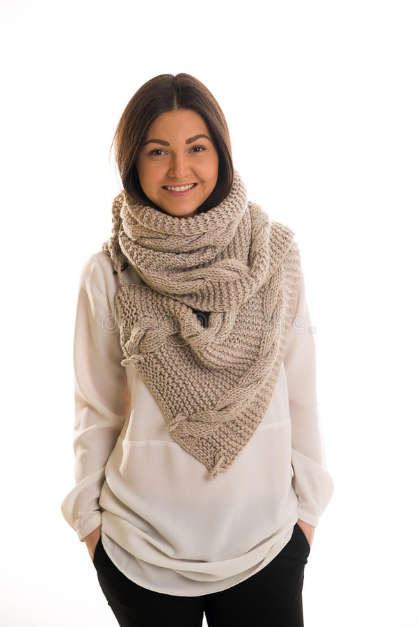 A girl in a grey knitted scarf smiling. A young woman in a grey knitted scarf smiling royalty free stock images