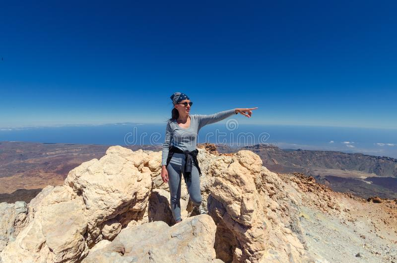 A girl in grey trousers and sweater on the top of the volcano te royalty free stock image