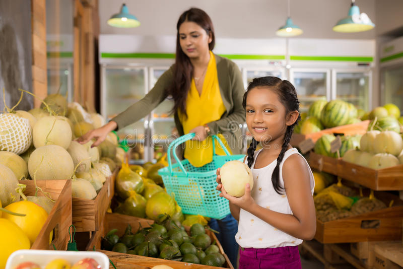 Girl at grocery store. Smiling Indian girl with a fresh melon standing at the grocery store royalty free stock images