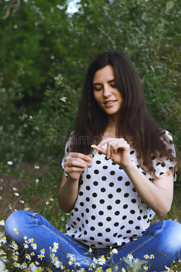 Girl guesses on camomile in nature. royalty free stock images