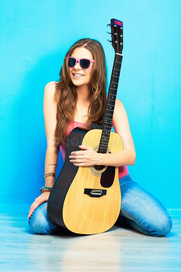 Girl with guitar against blue . hipster style portrait royalty free stock photography
