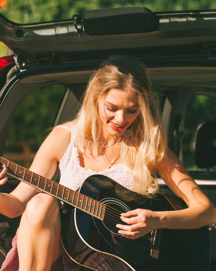 Girl with guitar on hatchback car. Travel vacation hitchhiking concept. Summer girl hippie style sitting on hatchback car with acoustic guitar stock images