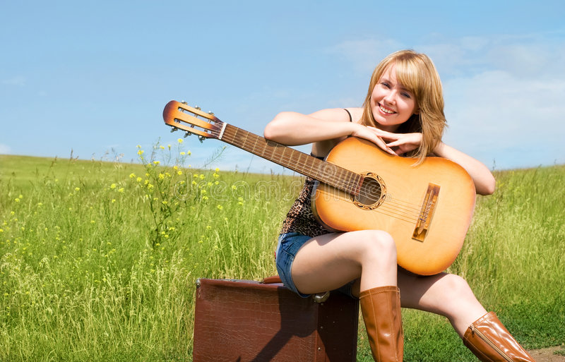 Girl with a guitar outdoor. Pretty blond girl wearing leathern boots sitting on the suitcase with a guitar outdoor royalty free stock images