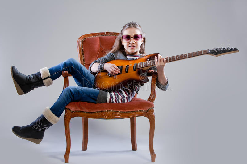 Girl with guitar and sunglasses. Playing as a rockstar stock image