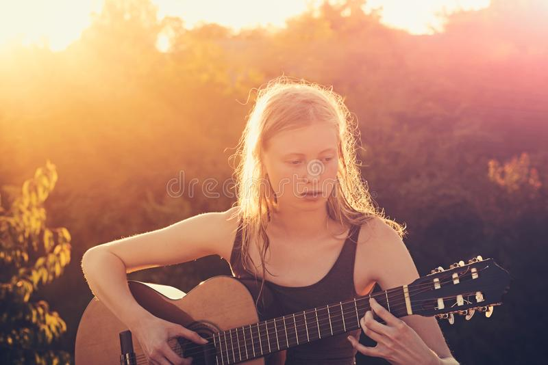 Girl guitarist playing guitar outdoor summer concept.  stock photography