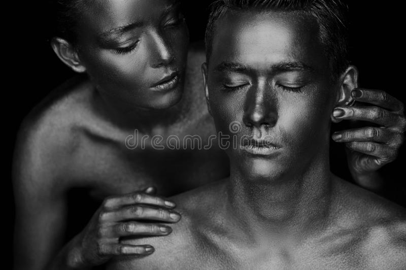 A girl and a guy covered in gold paint. With my eyes closed. The girl leaned, Black and white royalty free stock photo