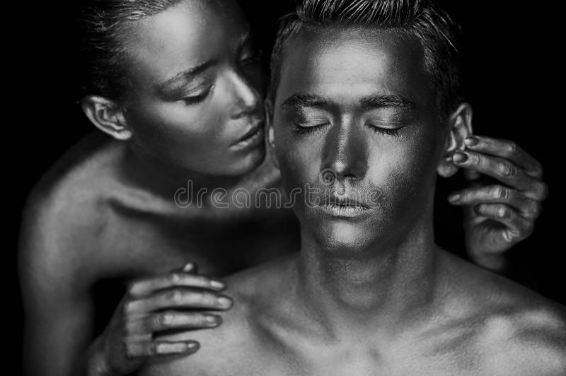A girl and a guy covered in gold paint. With my eyes closed. The girl leaned, Black and white stock photo