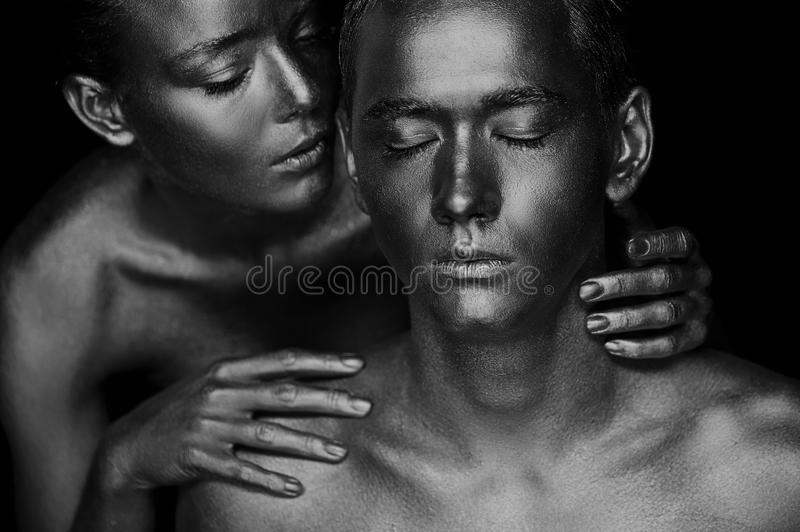 A girl and a guy covered in gold paint. With my eyes closed. The girl leaned, Black and white royalty free stock image