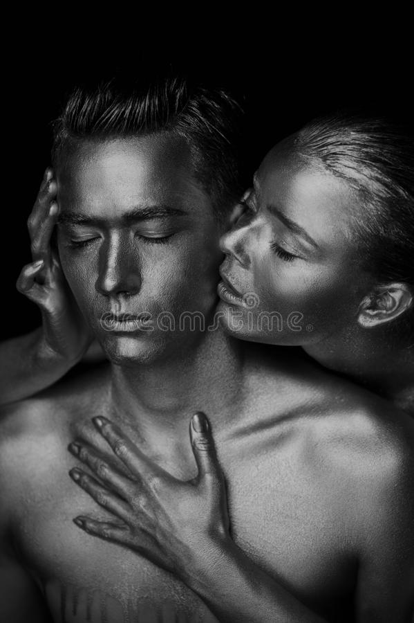 A girl and a guy covered in gold paint. With my eyes closed. The girl leaned, Black and white royalty free stock photography