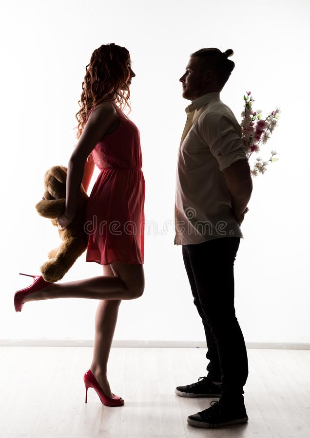Girl with a guy on a date. man holding flowers and woman holding teddy bear. silhouette on a light background royalty free stock images