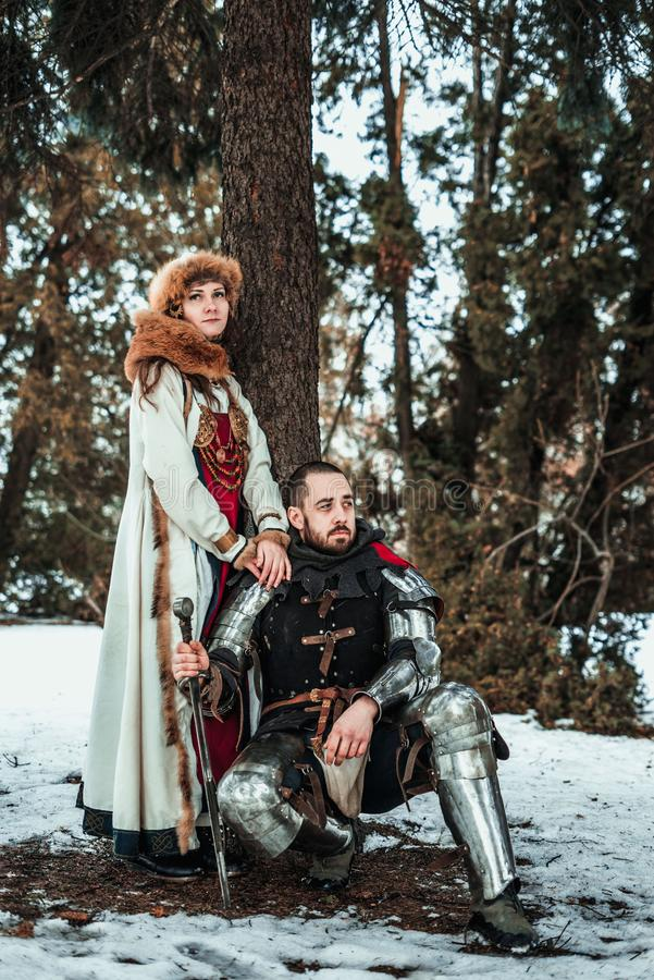 Girl and guy in historical costumes near a tree stock photos