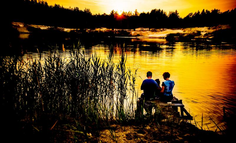 Girl and guy holding hands and sit on the shore of a forest lake royalty free stock photos