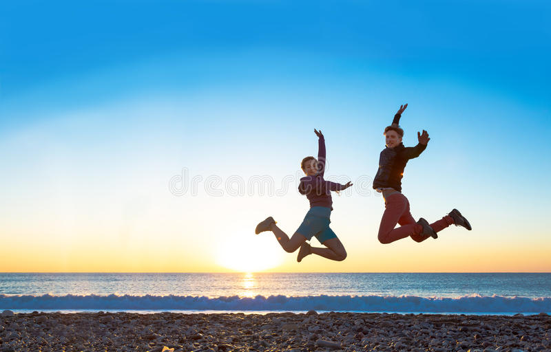 Girl and Guy jumping high with arms up spectacular sunrise at ocean coast stock image
