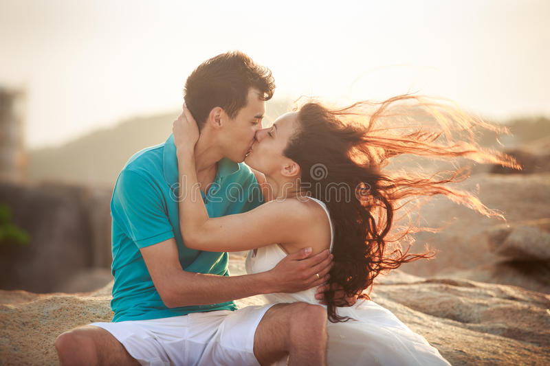 girl and guy kiss against rocks royalty free stock photos
