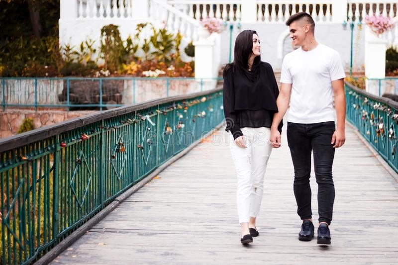 The girl and the guy walk on the bridge in the park royalty free stock image