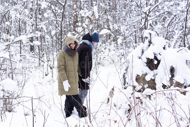 The girl with the guy are walking in a snowy forest. stock image