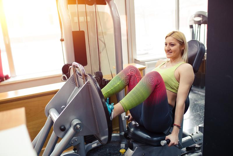 Girl in gym, exercising her legs. On a leg press royalty free stock images